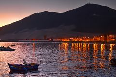 Man standing in boat rowing at late evening with coastal lights and mountains in background. Chimbote, Peru - April 17, 2018: Man standing in boat rowing at late Royalty Free Stock Photo