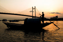 Man standing on a boat at the sunset. Man standing on a boat at sunset under bridge stock images