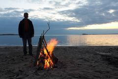 Man standing by the bonfire near the river at sunset Royalty Free Stock Photography