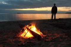 Man standing by the bonfire near the river at sunset Stock Photo