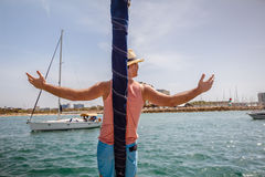 Man standing on a bow of sailboat with arms raised Stock Photos