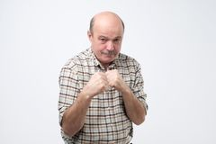 Man standing in boxer pose with raised fists as if defending or fighting. Mature bald man standing in boxer pose with raised fists as if defending or fighting stock photography