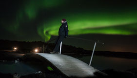 Watching the northern lights. Man standing on a bridge and watching the northern lights Stock Images