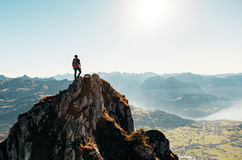 Man Standing on Brown Rocking Mountain Under Blue Sky and Yellow Sunlight Stock Photography