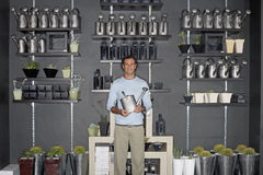 Man standing beside cacti display in shop, holding watering can, smiling, front view, portrait Stock Photography