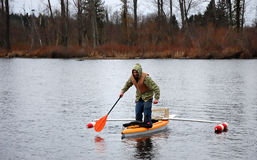 Man Standing in Canoe. This young man is standing in a canoe that has outriggers on it, trying to tip it over.  He's wearing a lifevest, and camoflauge Stock Photography