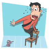 Man standing on chair afraid of rat. Stock Photo