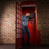 Man standing chatting in a phone booth Stock Image