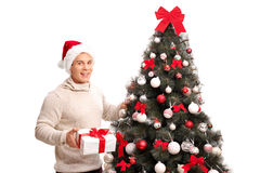 Man standing by a Christmas tree and holding a gift Stock Image