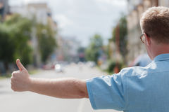 Man standing on the city street and hailing a taxi Royalty Free Stock Photos