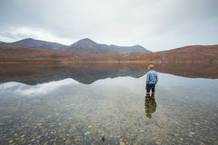 Man standing in clear lake surrounded by the Scottish Highlands. Man standing in beautiful clear loch in the Scottish Highlands in the Inner Hebrides, Isle of stock photo