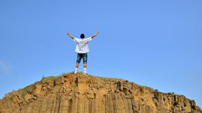 Man standing on cliff above blue sky Stock Photography