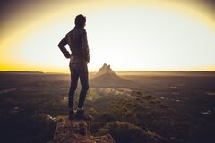 Man standing on cliff above valley stock photo
