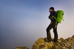 Man standing on a cliff in foggy weather Royalty Free Stock Photos