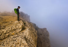 Man standing on a cliff in foggy weather Royalty Free Stock Photography