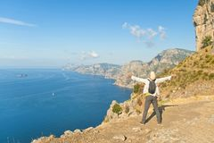 Man standing at cliff and looking at beautiful view. Young male tourist in white shirt and cap standing at cliff edge with his arms open looking at sea and Royalty Free Stock Images
