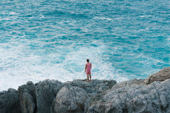 Man standing on the cliff on the shore of the ocean Royalty Free Stock Image