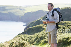 Man standing on cliff side path holding map Royalty Free Stock Images