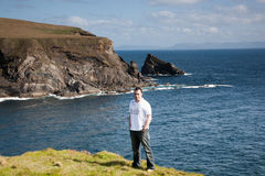 Man standing on cliff top in Donegal. Man in a white t-shirt standing in a field by the sea on a cliff top in Donegal, Ireland, blue sky and thin cloud stock images