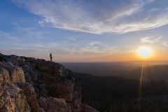 Man Standing on Cliff Watching Sunrise Stock Image
