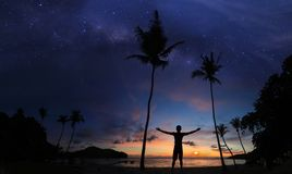 Man standing on the coconut beach with a million stars and sunrise early morning. Panoramic landscape stock images