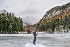 Man standing with cold winter view, snow and ice on cloudy day. Man standing with icy lake, trees in cold winter and beautiful view, snow and ice on cloudy day Royalty Free Stock Images