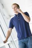 Man standing in corridor smiling using phone Stock Photos