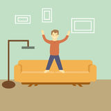 Man standing on the couch in his flat with a lamp and pictures Stock Image