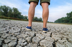 Man standing on cracked ground during summer drought Royalty Free Stock Images