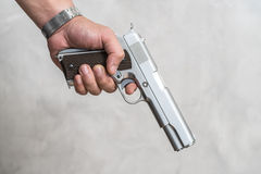 A man standing on a criminal with a gun in his hand.  Stock Photo