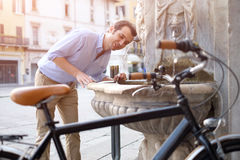 Man is standing crossing the city street. Man is resting next to his bike in the city street Royalty Free Stock Photography