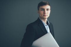 Man standing on dark background with laptop in hands Royalty Free Stock Image