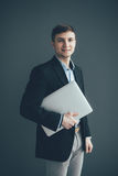 Man standing on dark background with laptop in hands Royalty Free Stock Photos
