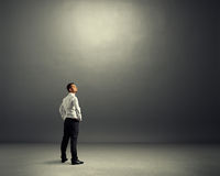 Man standing in the dark grey room. Young businessman standing in the dark grey room and looking up Stock Images