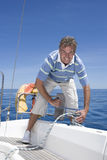 Man standing on deck of sailing boat out to sea, winding rope pulley of boat rigging, smiling, front view, portrait Stock Photos
