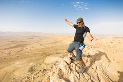 Man standing desert mountain cliff edge. Stock Image