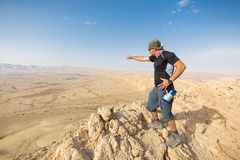 Man standing desert mountain cliff edge. Stock Photos