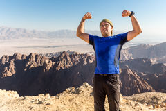 Man standing desert mountain summit posing strong hands victory. Royalty Free Stock Photos