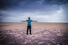 Man standing in desert with open arms Stock Image