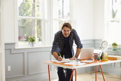 Man Standing At Desk Working At Laptop In Home Office Royalty Free Stock Image