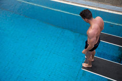Man standing on diving board at public swimming pool Stock Photos