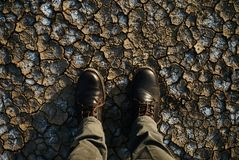 Man standing on a dry cracked earth. Feet in boots and jeans standing on the cracked soil, top view. Environment and natural concept Royalty Free Stock Images