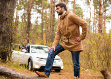 Man standing on dry log in forest. Young bearded man standing on the big dry log on forest road with blurred white car on background Royalty Free Stock Photo