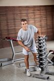 Man Standing By Dumbbells In Rack Royalty Free Stock Photo