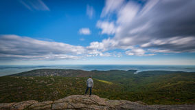 Man standing at the edge of Cadillac Mountain. Long exposure with cloud movement as a man looks at the beauty Cadillac mountain has to offer Royalty Free Stock Photo