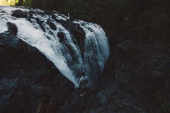 Man standing on the edge of the cliff in forest with waterfall royalty free stock images