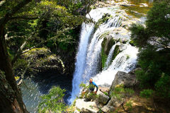 Man standing on edge of waterfall in New Zealand. Royalty Free Stock Photography