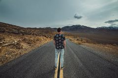 Man standing on empty desert asphalt road waiting and thinking. View from the back.  Stock Images