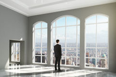 Man standing in an empty loft interior and looking to the city Royalty Free Stock Photo