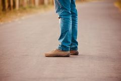 Man standing on an empty road wearing jeans pants. A man is standing on an empty road wearing jeans pants and shoes unique stock photograph royalty free stock photography